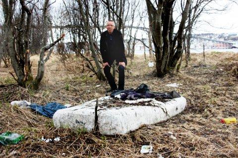 Her ligger en madrass og plastikk slengt rundt i skogholtet nedenfor Mandelasletta i Tromsø. John Pedersen i Tromsdalen bydelsråd er fortvilet. Foto: Stian Saur