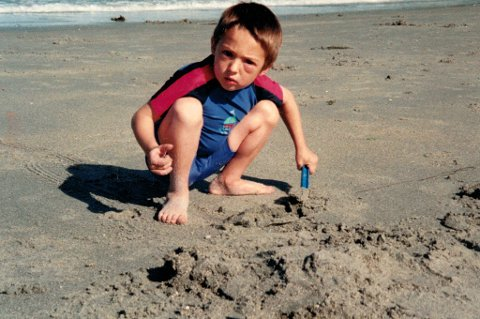 Adam Ismael Wenham som liten gutt, tilsynelatende lekende på stranda som en hvilken som helst annen gutt. 15 måneder gammel fikk tromsøgutten en alvorlig hjerneskade etter å ha blitt påkjørt to ganger, og legene trodde ikke han ville overleve. Nå har han blitt 19 år, og kjemper om medalje i bassenget i Rio.