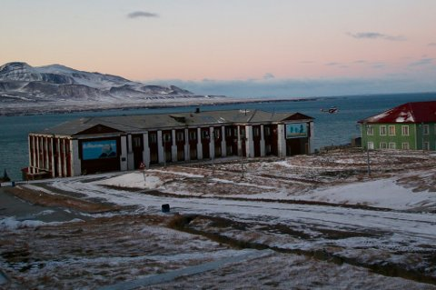 SØKER: Et av Sysselmannens redningshelikoptre søker langs strandkanten i Barentsburg søndag formiddag. Foto: Øystein Solvang