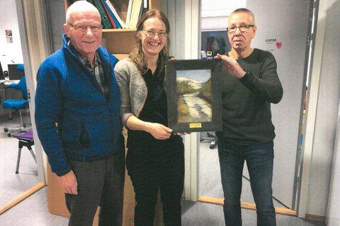 Torstein Myhre (til venstre) og John Pedersen i Tromsdalen bydelsråd gir her Hanne Johnsen det synlige beviset på at hun er Årets tromsdaling 2017. Foto: Privat