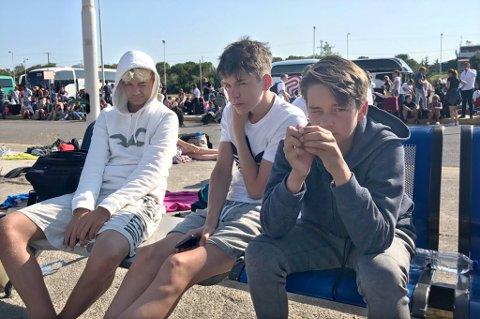 VENTER PÅ FLY: Flytrafikken til og fra Kos er kraftig forsinket som følge av jordskjelvet. Her sitter Sjur Falck, Johann Haumann og Mikkel Falck og venter i sola. - Vi har det bra, og er glade for at ingen ble skadet, sier mamma Laila Falck.