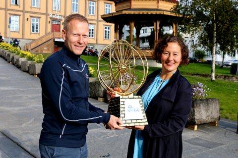 Tromsø-ordfører Kristin Røymo mottar Arctic Race of Norway-trofeet fra daglig leder Knut-Eirik Dybdal. Tromsø får ha trofeet helt til neste års startkommune er annonsert over nyttår.