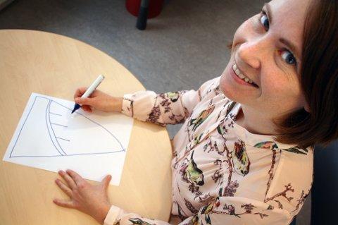 Åsta Sortland viser hvor enkelt et forslag til nytt kommunevåpen kan tegnes, her med Gisundbrua som motiv.