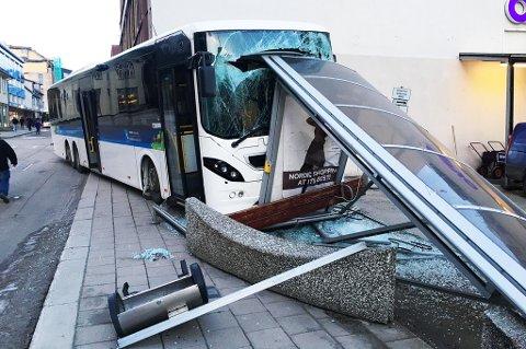 Bussen har kommet opp på fortauet, knust et busskur og står nå fast under hushjørnet på Austadbygget i Tromsø sentrum. Foto: Stian Saur