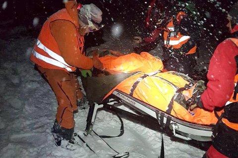 NESTEN NEDE: Her blir mannen plassert i pulk, og trukket ned fra fjellet av snøskuter. En liten halvtime senere var de nede.