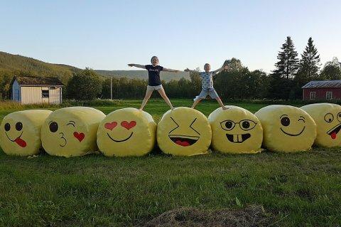 SMILEY: Matilde (10) og Matias (9) på toppen av familiens rundballer. De gule smilefjes-rundballene har blitt lagt merke til. Foto: Privat