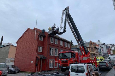 VILLE IKKE NED: En politi- og en brannmann forsøker å få mannen ned fra taket.