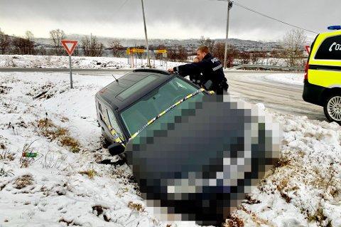 Her jobber politiet med å sikret bilen som ligger i grøfta i krysset i Finnvika på Kvaløya. Foto: Stian Saur