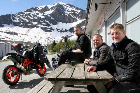 PÅ MOTORSYKKEL: Tromsøgjengen Johannes Køhler (t.v.), Vidar Karlsen og Håvard Sørgård Hansen nyter sola utenfor butikken i Senjahopen.