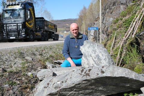 FRYKTER ULYKKE: Det er ikke akkurat småstein Arne Mathisen viser fram i veigrøfta ved Stibergan, der trafikken mellom Sørreisa og Finnsnes dundrer forbi på fylkesvei 86.