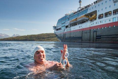 Lewis Pugh, verdenskjent svømme-pioner, blir Hurtigrutens miljø-ambassadør. Her svømmer han omkapp med hurtigruteskipet Midnatsol i Rystraumen.