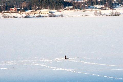 KALDT OG KLART: En ensom isfisker på Mjøsisen ved Sveastranda søndag ettermiddag.