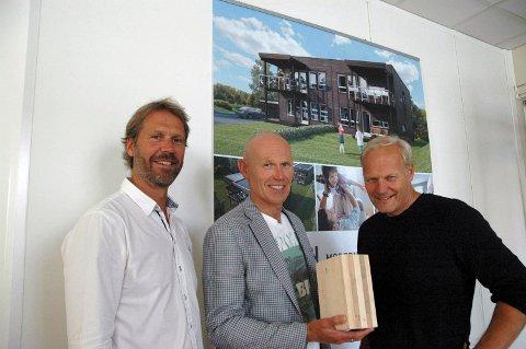 Henning Jørgentvedt (f.v), Oddvar Haugen og Jon Kveseth i Nordbolig foran skissen av flermannsboligen på Raufoss som skal sette standarden for deres massivhusprosjekter.