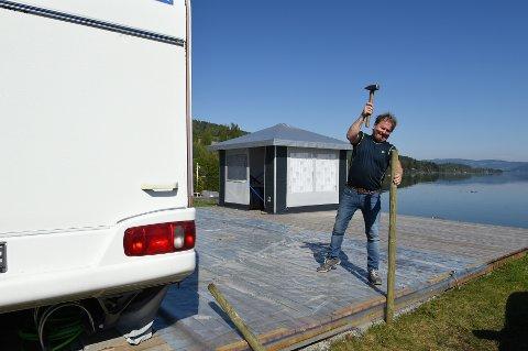 Sikrer: Torbjørn Flo bruker påler for å sikre plattingen ved campingvogna på Sveastranda. Foto: Henning Gulbrandsen.