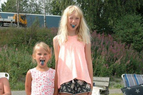 BADING ER BEST: Adele (6) og Marthe (10) viser frem tunger som matcher fargen på himmelen denne sommeren. Det de liker best med båt-ferie er å bade.