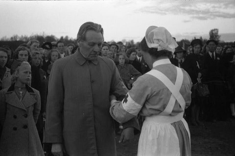 SKIFTE: En ukjent sykepleier fester Milorgs armbind på sogneprest Ingebrigt Hole, trolig under et arrangement på Lena Idrettsplass i mai-dagene 1945.