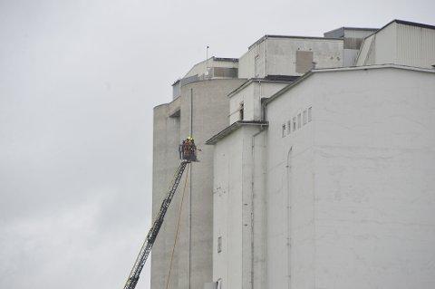 KREVENDE SLUKKING: Brannen i kornsiloen på Lena er vanskelig å slukke på grunn av bygningsmessige forhold. Bildet er tatt ved 12-tiden tirsdag. Brannmannskap løftes opp i etasjene i forsøket på å komme til varmekildene.