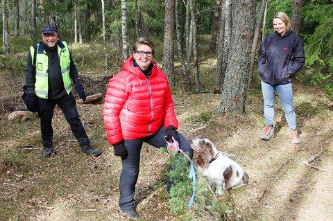 HUNDEHJØRNET: De blå båndene i skogen på Møllerenga viser hvor det ett mål store Hundehjørnet skal etableres. Ordfører Hanne Opdan, her med Oso, har allerede meldt seg på dugnadsgjengen. Her med skogbestyrer Reidar Haugen og utvalgsleder Camilla Hille.