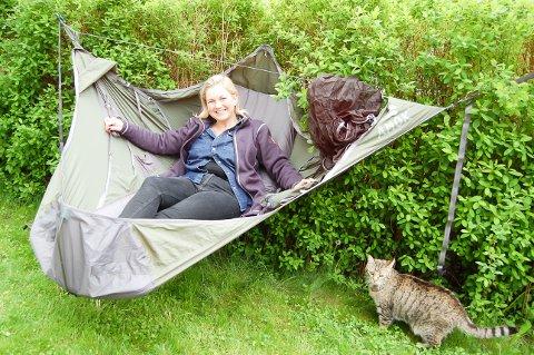 I HEKKEN: Til ære for fotografen henger Ina Christine Lindahl opp hengekøye hjemme i sin egen hage, selv om det ikke er ideelt med hekk mellom trærne. Katten Daisy følger nysgjerrig med på matmors krumspring.