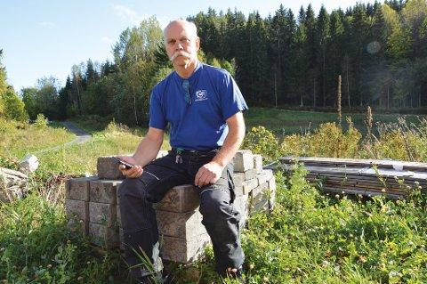 Hansen eier Guttås (bak ham på bildet) og donerer den gjerne som grunn for en ny basestasjon. Bare det kan gi ham bedre mobildekning enn han har i nå.