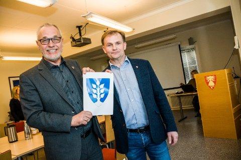 Tormod Henriksen fra Svarstad har laget det nye kommunevåpenet. Her presentert av Rune Høiseth (t.v.) og Knut Olav Omholt.