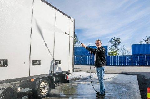 LETTET: Den nye målingen viser at daglig leder Even Hvaal nå kan høytrykksspyle biler og maskiner uten å overskride støygrensene. I bakgrunnen ses containerne som Hvaal har satt opp for å redusere lyden mot naboene i øst.