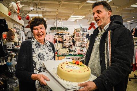 STEMT FRAM AV KUNDENE: - Brit Brathagen på Miniklær har drevet med super service i snart 40 år, det vet kundene å sette pris på, sier Larvik bys Paal Espen Wingaard, og troppet opp med kake.