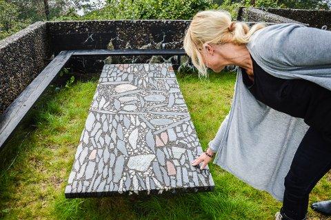 FABRIKK I REKKEVIK: Erling Viksjø og Odd Tandberg laget bordplater og fasader i det de kalte conglo, med mønstre av stein i betongplater, som dette bordet som Mari Viksjø Grøstad viser fram på hytta. (arkivfoto)