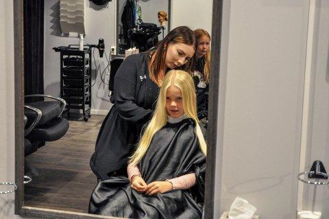 ENDELIG: Frisør Sanne Sørensen tok fatt på Amelia Strøms lange lyse hår, og klipte bort 26 centimeter til en ny parykk. I bakgrunnen venninne Aurora Helland Sørensen.