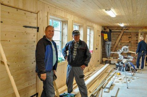 Helge Saga (t.v.) og Hans Willy Lunde legger lister rundt den nye låvedøra på Lardal bygdetun. Snart står hele låven ferdig til å brukes av befolkningen.