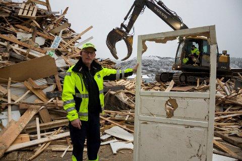 Jørn Atle Nysveen i HRA ved haugen med innlevert trevirke. Døra han holder gir ikke brukbar flis, og inneholder i tillegg mye metall.