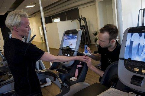 Tom Erik Lukkedal tar en lactatprøve fra fingeren til Kristin Søraker. Prøven viser hvor mye melkesyre hun har i kroppen, og kan gi viktig informasjon om hvor høy puls hun bør trene på.