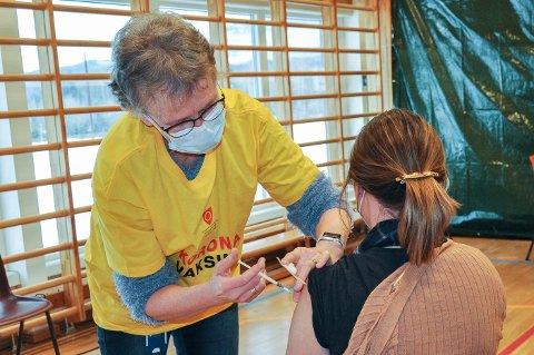 GLAD FOR MANGE HJELPERE: Her setter Kristin Andresen selv en korona-vaksine. Hun er overveldet over alle som har meldt seg for å gjøre denne jobben. Dette bildet er tatt under vaksinasjon på Sokna tidligere i vår.