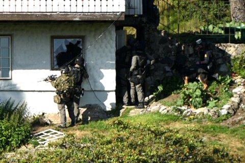 PÅ VEI INN: Her er politeit på vei inn i et vindu på huset de mener en mann har forskanset seg. FOTO: VIDAR SANDNES