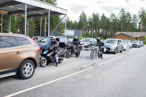 Biler og motorsykler venter i kø for å vise passet på vei tilbake over grensen til Norge 25. juli, den første dagen Värmland ble erklært grønn igjen. Nå er regionen rød, og det er slutt på kontrollene. Foto: Annika Byrde (NTB scanpix)