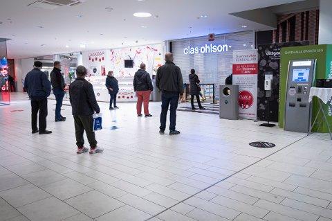 KØ: Det var kø utenfor flere av butikkene på Strømmen storsenter torsdag morgen. Her venter kundene på butikkåpning med god avstand til sidemann.