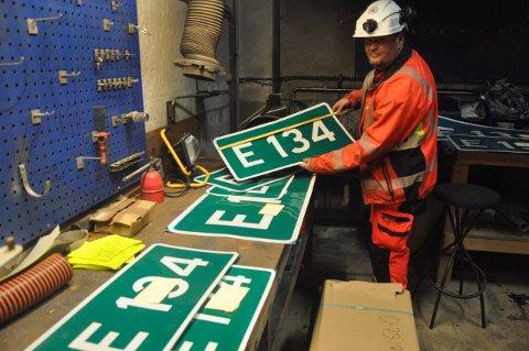 KLARGJØR: Lars Olsson iferd med å klargjøre klistremerker som skal monteres på skiltene som angir veinummer fra Lier til Oslofjordtunnelen.