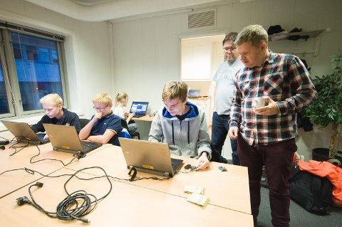 FÅR PRØVE: Ludvig Sørlie (17) får teste mikrodatamaskinen micro:bit, som er utviklet av den engelske rikskringkasteren BBC. Bak står Roger Riksheim Berg (bakerst) og Terje Rove Pettersen og veileder 17-åringen.