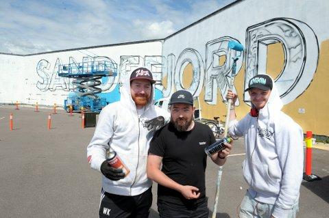 Utsmykning: Graffitimalerne Kim Andre Kolstad (28), Manny Hyttvik (32) og Thorvald Heum (27) til høyre er i gang med veggkunsten nederst i Museumsgata.