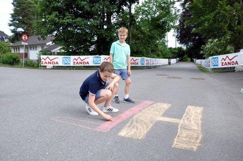 MALER: Markus Holden (11) og William Holden (8) forbereder seg til siste dag av sykkel-NM med å male gata fin til søndagens ritt.