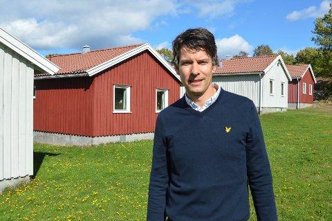 VEDLIKEHOLD: Daglig leder ved Strand Leirsted og Gjestegård Ruben Heitmann, forklarer at stedet sårt trenger oppussing. Hyttene bak ham er fra 1960-tallet, og det har blitt gjort lite for å holde dem ved like.