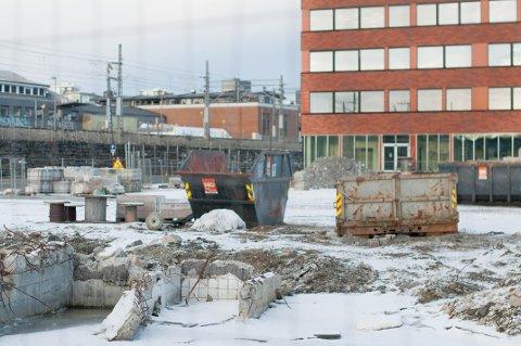 Her skulle det bygges parkeringshus, men nå ser det ut som en byggeplass. Ordføreren lover at tomten skal ryddes og gi plass til parkeringsplasser.