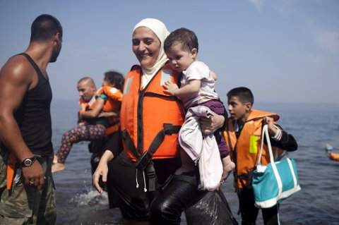A Syrian refugee holds a child moments after arriving on a dinghy on the Greek island of Lesbos, September 3, 2015. Greece will ask the European Union for about 700 million euros to build infrastructure to shelter the hundreds of refugees and migrants arriving on its shores daily, the government said on Thursday. The cash-strapped country has seen a rise in the number of refugees and migrants -- mostly from Syria, Iraq and Afghanistan -- arriving on rubber dinghies from nearby Turkey. REUTERS/Dimitris Michalakis