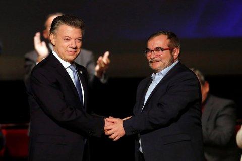 President og fredsprisvinner Juan Manuel Santos (t.v.) og FARC-lederen Timoleón Jiménez, hvis egentlige navn er Rodrigo Londoño Echeverri, tar hverandre i hånden etter at den nye utgaven av fredsavtalen ble undertegnet i Bogota 24. november.