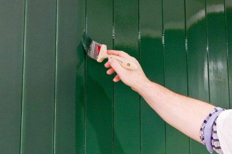 Bruk en skrå pensel i hjørner og til å påføre maling i panelets profiler.
