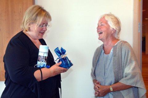 Astrid Nøklebye Heiberg overrekker daværende kommunalminister Erna Solberg et legohus og en handlingsplan for seniorpolitikk.