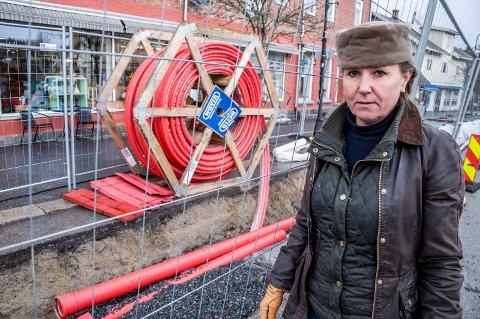 KABELGRØFT: Hilde Nyborg Braarud ved kabelgata som nå graves gjennom Ørje sentrum. Hun har bolig og forretningseiendom tett opp mot kabeltraseen i Storgata.