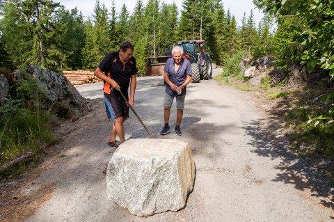 STEIN: - Nå skal det være umulig å komme forbi, fastslår Thore Skoglund (t.v.) og Nils Skogstad etter å ha plassert en stor stein midt i veien som bomsnikere bruker.