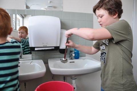 Johannes Fog og Elias Mellegård hjelper hverandre med å vaske hendene, ettersom det ikke er vann i springen.