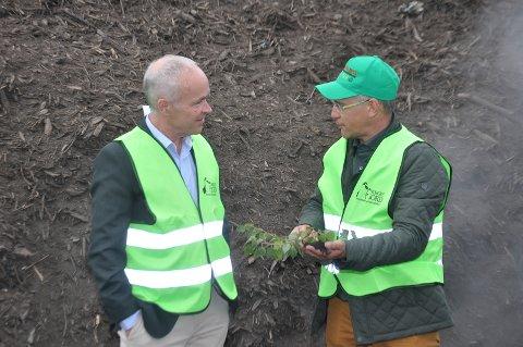 Tore D. Carlsen forklarer finansminister Jan Tore Sanner  hvordan han lager kompost av organisk hageavfall ved sin jordfabrikk på Momarken.